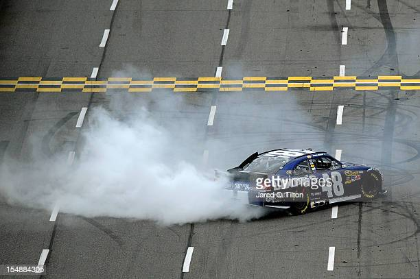 Jimmie Johnson driver of the Lowe's Chevrolet celebrates with a burnout after winning the NASCAR Sprint Cup Series Tums Fast Relief 500 at...