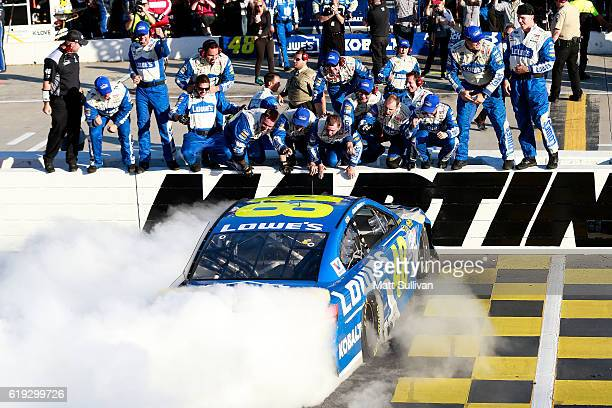 Jimmie Johnson driver of the Lowe's Chevrolet celebrates with a burnout after winning the NASCAR Sprint Cup Series Goody's Fast Relief 500 at...