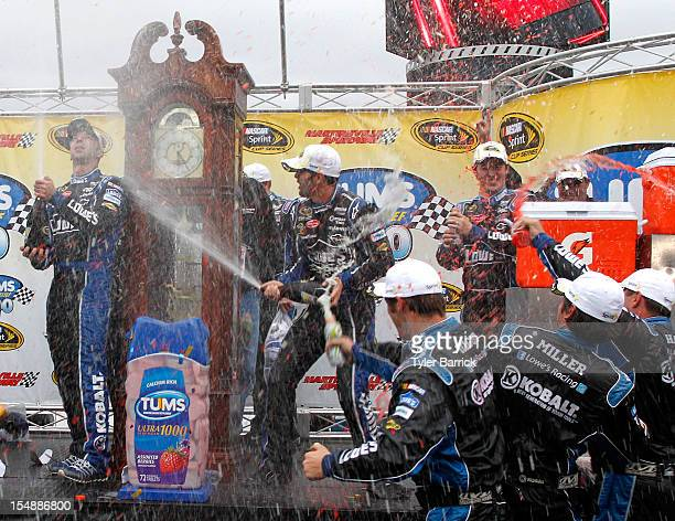 Jimmie Johnson driver of the Lowe's Chevrolet celebrates with crew chief Chad Knaus and crew members in Victory Lane after winning the NASCAR Sprint...