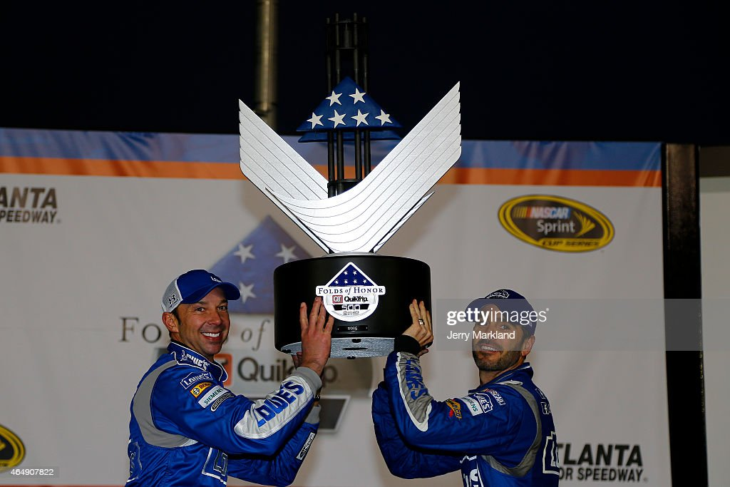 Jimmie Johnson, driver of the #48 Lowe's Chevrolet, celebrates with his crew chief, Chad Knaus, in victory lane after winning the NASCAR Sprint Cup Series Folds of Honor QuikTrip 500 at Atlanta Motor Speedway on March 1, 2015 in Hampton, Georgia.