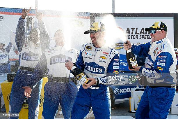 Jimmie Johnson driver of the Lowe's Chevrolet celebrates with champagne in Victory Lane after winning the NASCAR Sprint Cup Series Folds of Honor...