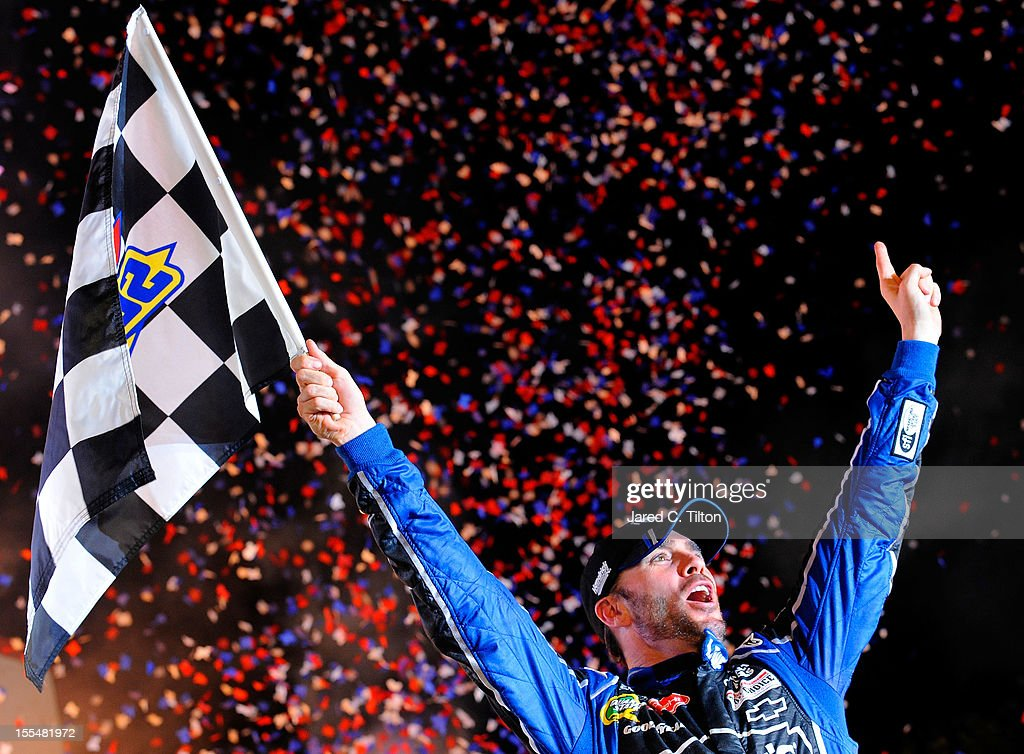 Jimmie Johnson, driver of the #48 Lowe's Chevrolet, celebrates with the checkered flag in Victory Lane after winning the NASCAR Sprint Cup Series AAA Texas 500 at Texas Motor Speedway on November 4, 2012 in Fort Worth, Texas.
