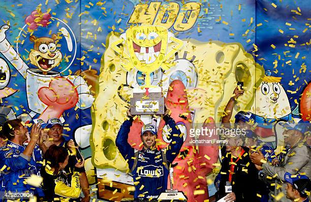 Jimmie Johnson, driver of the Lowe's Chevrolet, celebrates with the trophy in Victory Lane after winning the NASCAR Sprint Cup Series SpongeBob...