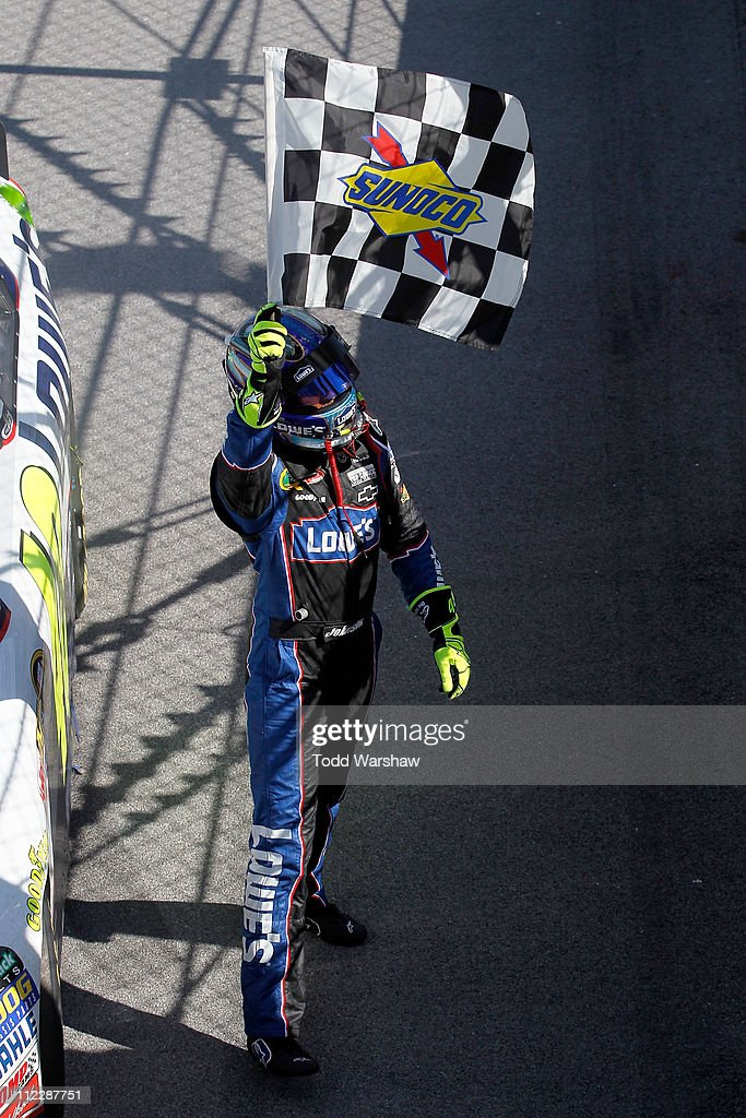 Jimmie Johnson, driver of the #48 Lowe's Chevrolet, celebrates with the checkered flag after winning the NASCAR Sprint Cup Series Aaron's 499 at Talladega Superspeedway on April 17, 2011 in Talladega, Alabama.