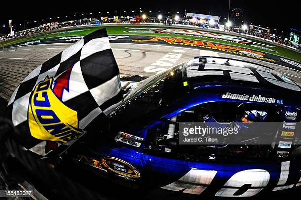 Jimmie Johnson driver of the Lowe's Chevrolet celebrates with the checkered flag after winning the NASCAR Sprint Cup Series AAA Texas 500 at Texas...
