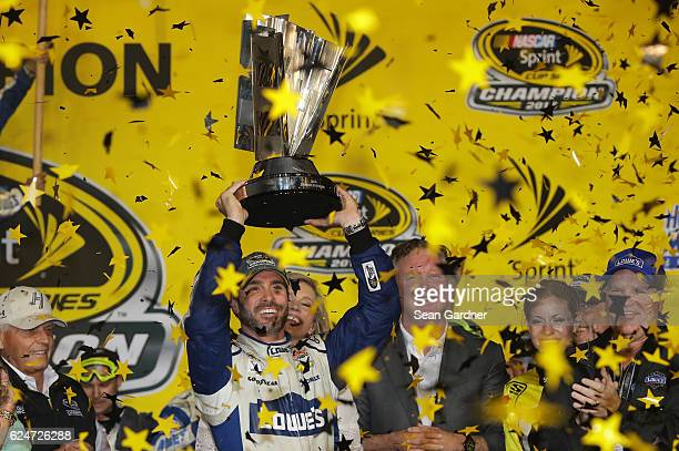 Jimmie Johnson driver of the Lowe's Chevrolet celebrates with the NASCAR Sprint Cup Series Championship trophy in Victory Lane after winning the...