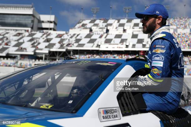 Jimmie Johnson driver of the Lowe's Chevrolet climbs into his car on the grid during prerace ceremonies for the weather delayed Monster Energy NASCAR...