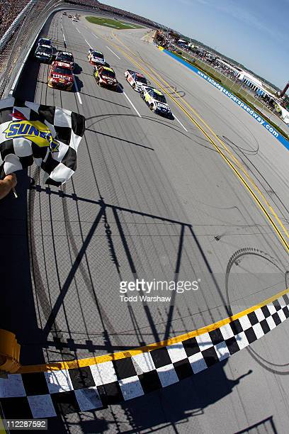 Jimmie Johnson driver of the Lowe's Chevrolet crosses the finish line ahead of Clint Bowyer driver of the BBT Chevrolet and Jeff Gordon driver of the...