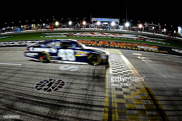 Jimmie Johnson driver of the Lowe's Chevrolet crosses the finish line to win the NASCAR Sprint Cup Series AAA Texas 500 at Texas Motor Speedway on...