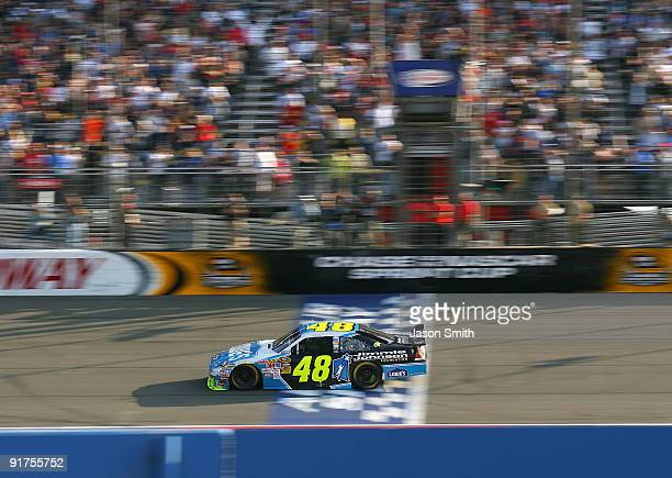 Jimmie Johnson driver of the Lowe's Chevrolet crosses the finish line to win the NASCAR Sprint Cup Series Pepsi 500 at Auto Club Speedway on October...