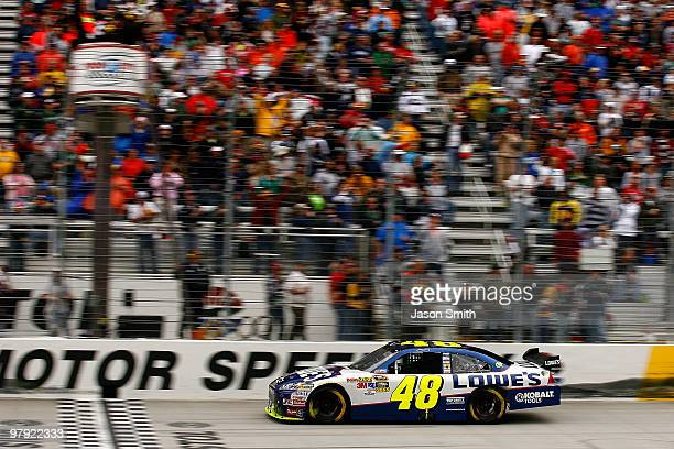Jimmie Johnson driver of the Lowe's Chevrolet crosses the finish line to win the NASCAR Sprint Cup Series Food City 500 at Bristol Motor Speedway on...