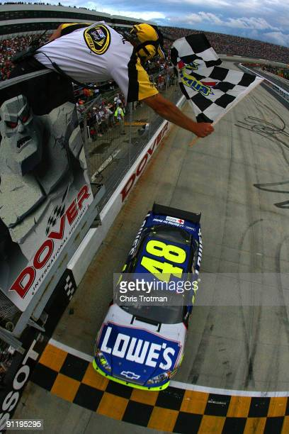 Jimmie Johnson driver of the Lowe's Chevrolet crosses the start/finish line to take the checkered flag to win the NASCAR Sprint Cup Series AAA 400 at...