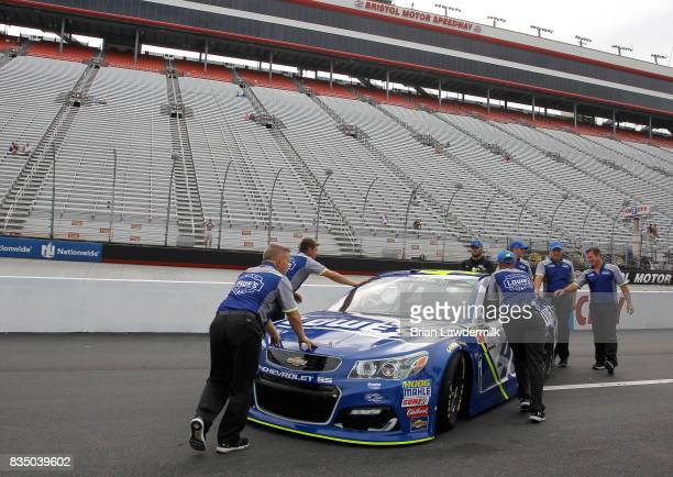 Jimmie Johnson driver of the Lowe's Chevrolet has his car pushed down pit lane during practice for the Bass Pro Shops NRA Night Race at Bristol Motor...
