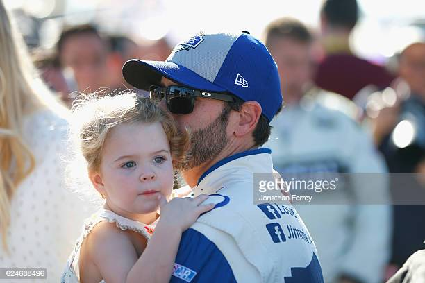 Jimmie Johnson driver of the Lowe's Chevrolet holds his daughter Lydia Norriss during prerace ceremonies for the NASCAR Sprint Cup Series Ford...