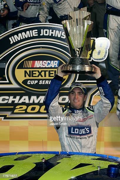 Jimmie Johnson driver of the Lowe's Chevrolet holds the championship trophy over his head arter clinching the NASCAR Nextel Cup Series Championship...