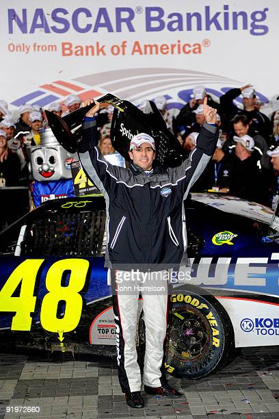 Jimmie Johnson driver of the Lowe's Chevrolet holds up the trophy after winning the NASCAR Sprint Cup Series NASCAR Banking 500 at Lowe's Motor...