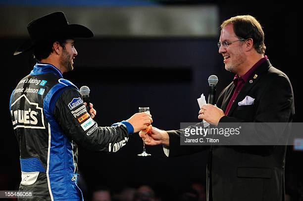 Jimmie Johnson driver of the Lowe's Chevrolet is presented with a glass of champagne by Texas Motor Speedway President Eddie Gossage during the...