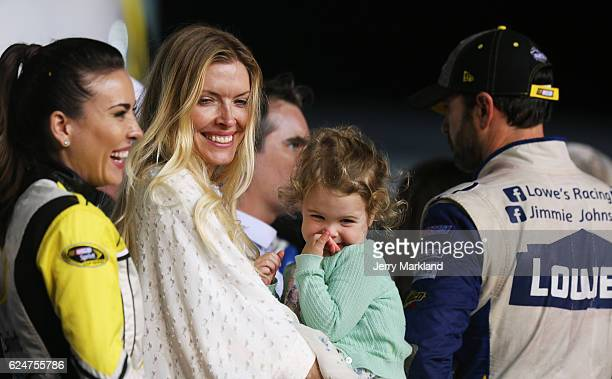Jimmie Johnson driver of the Lowe's Chevrolet is seen in Victory Lane with his wife Chandra and daughter Lydia Norriss after winning the NASCAR...