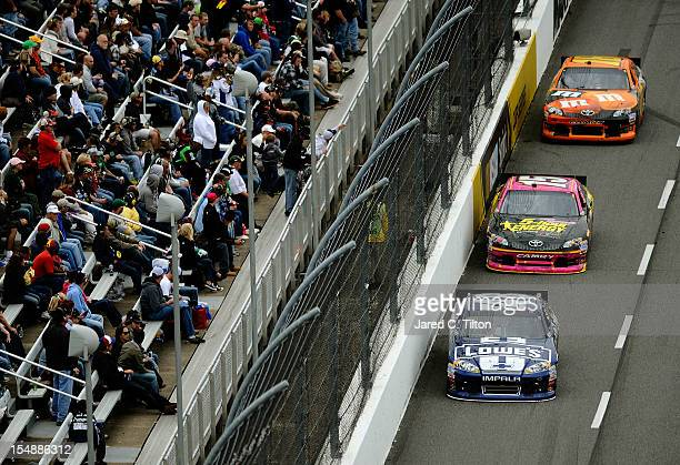 Jimmie Johnson driver of the Lowe's Chevrolet leads Clint Bowyer driver of the 5Hour Energy Benefiting Avon Foundation for Women Toyota and Kyle...
