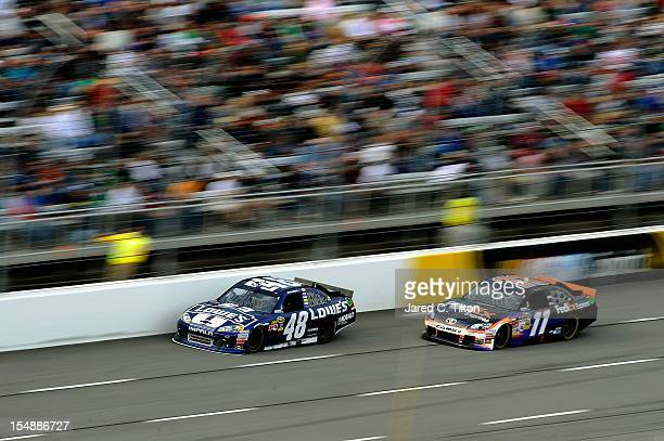 Jimmie Johnson driver of the Lowe's Chevrolet leads Denny Hamlin driver of the FedEx Express Toyota during the NASCAR Sprint Cup Series Tums Fast...