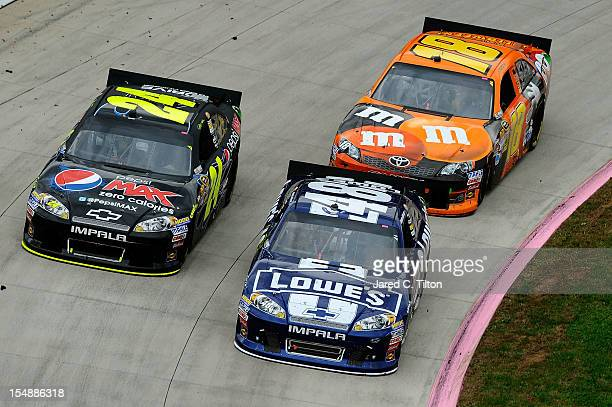Jimmie Johnson driver of the Lowe's Chevrolet leads Jeff Gordon driver of the Pepsi Max Chevrolet and Kyle Busch driver of the MM's Halloween Toyota...
