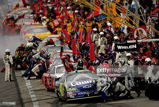 Jimmie Johnson, driver of the Lowe's Chevrolet, makes a pit stops in front of a line of cars during the NASCAR Nextel Cup Series LifeLock 400 at...