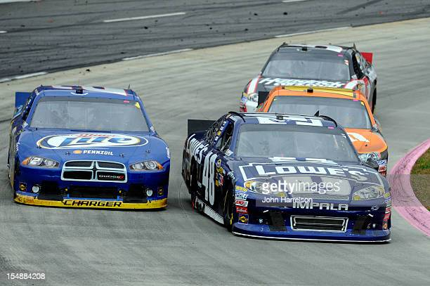 Jimmie Johnson driver of the Lowe's Chevrolet passes Brad Keselowski driver of the Miller Lite Dodge for the lead during the NASCAR Sprint Cup Series...