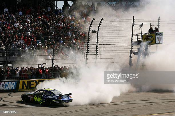 Jimmie Johnson, driver of the Lowe's Chevrolet, performs a burnout on the track after winning the NASCAR Nextel Cup Series Jim Stewart 400 at...