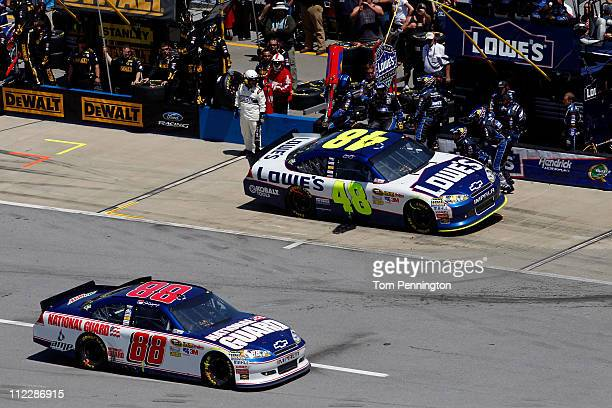 Jimmie Johnson driver of the Lowe's Chevrolet pits as Dale Earnhardt Jr drives the National Guard/Amp Energy Chevrolet down pit road during the...