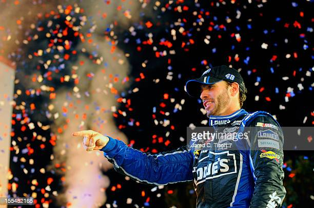 Jimmie Johnson driver of the Lowe's Chevrolet points to his crew in Victory Lane after winning the NASCAR Sprint Cup Series AAA Texas 500 at Texas...