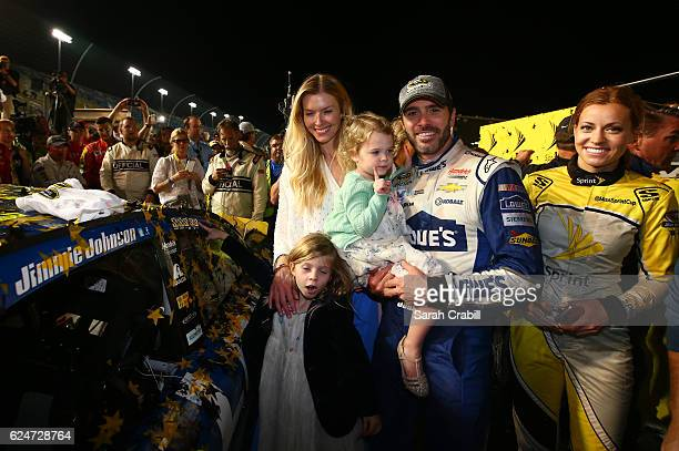 Jimmie Johnson driver of the Lowe's Chevrolet poses in Victory Lane with his wife Chandra and daughters Genevieve Marie and Lydia Norriss after...