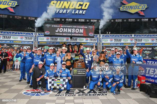 Jimmie Johnson driver of the Lowe's Chevrolet poses with his crew in Victory Lane after winning the Monster Energy NASCAR Cup Series O'Reilly Auto...