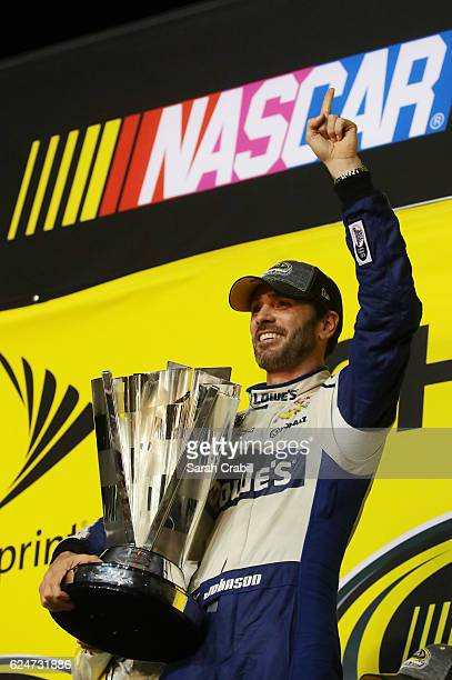 Jimmie Johnson, driver of the Lowe's Chevrolet, poses with the NASCAR Sprint Cup Series Championship trophy in Victory Lane after winning the NASCAR...