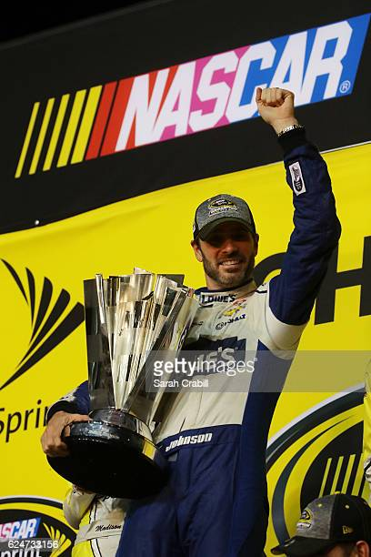 Jimmie Johnson driver of the Lowe's Chevrolet poses with the NASCAR Sprint Cup Series Championship trophy in Victory Lane after winning the NASCAR...