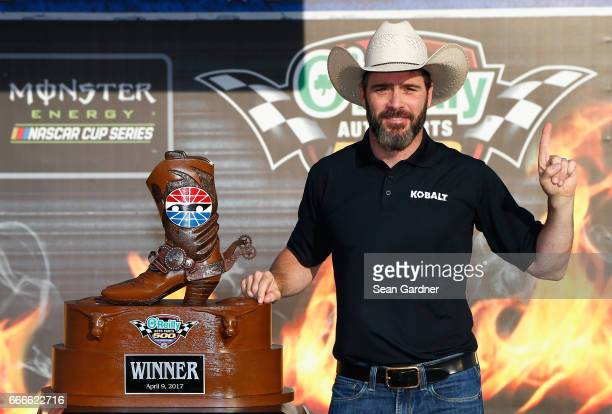 Jimmie Johnson driver of the Lowe's Chevrolet poses with the trophy in Victory Lane after winning the Monster Energy NASCAR Cup Series O'Reilly Auto...