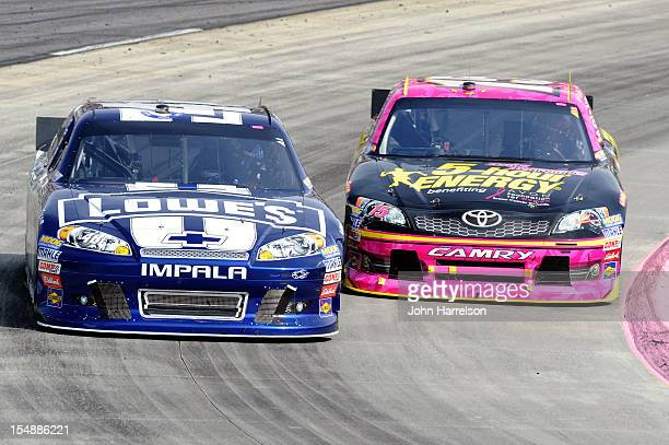 Jimmie Johnson driver of the Lowe's Chevrolet races Clint Bowyer driver of the 5Hour Energy Benefiting Avon Foundation for Women Toyota during the...