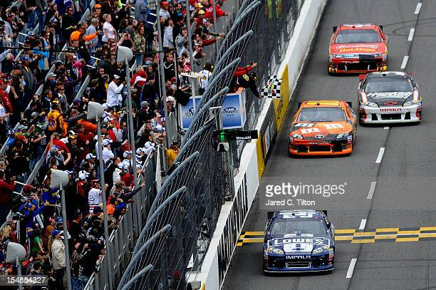 Jimmie Johnson driver of the Lowe's Chevrolet races past the checkered flag to win the NASCAR Sprint Cup Series Tums Fast Relief 500 at Martinsville...