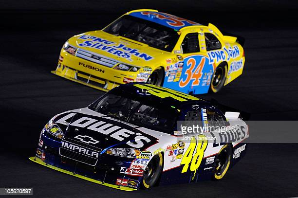 Jimmie Johnson, driver of the Lowe's Chevrolet, races Travis Kvapil, driver of the Long John Silver's Ford, during the NASCAR Sprint Cup Series Bank...