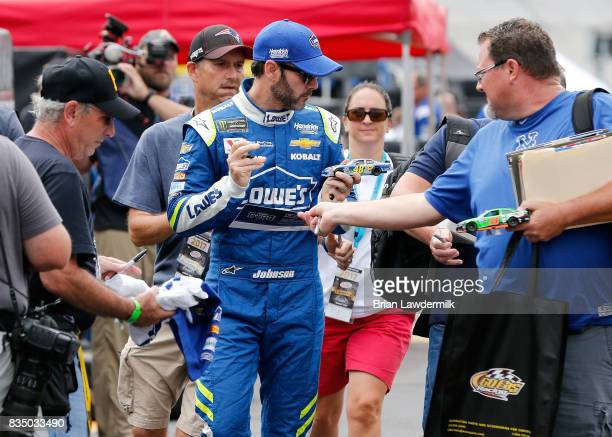 Jimmie Johnson driver of the Lowe's Chevrolet signs autographs during practice for the Bass Pro Shops NRA Night Race at Bristol Motor Speedway on...