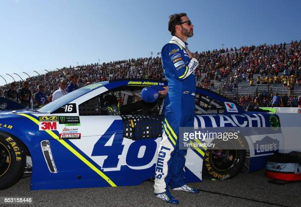 Jimmie Johnson driver of the Lowe's Chevrolet stands for the national anthem during prerace ceremonies for the Monster Energy NASCAR Cup Series ISM...