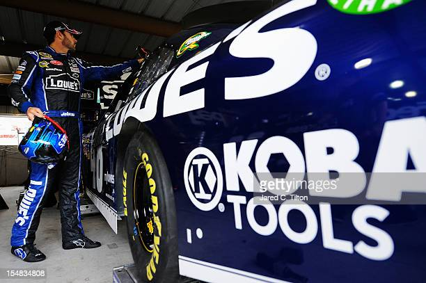 Jimmie Johnson driver of the Lowe's Chevrolet stands in the garage area during practice for the NASCAR Sprint Cup Series Tums Fast Relief 500 at...