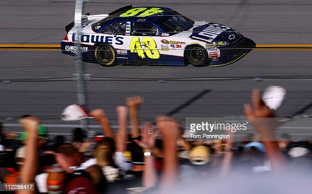 Jimmie Johnson driver of the Lowe's Chevrolet takes a victory lap as fans cheer after winning the NASCAR Sprint Cup Series Aaron's 499 at Talladega...