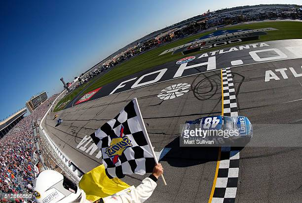 Jimmie Johnson driver of the Lowe's Chevrolet takes the checkered and yellow flags to win the NASCAR Sprint Cup Series Folds of Honor QuikTrip 500...