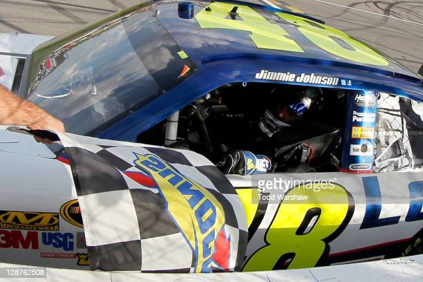 Jimmie Johnson, driver of the Lowe's Chevrolet, takes the checkered flag from a NASCAR official after winning the NASCAR Sprint Cup Series Hollywood...