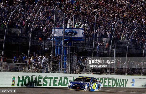 Jimmie Johnson, driver of the Lowe's Chevrolet, takes the checkered flag to win the NASCAR Sprint Cup Series Ford EcoBoost 400 and the 2016 NASCAR...