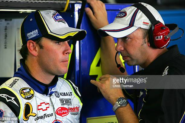 Jimmie Johnson driver of the Lowe's Chevrolet talks with his crew chief Chad Knaus during practice for the NASCAR Nextel Cup Series Pocono 500 at...