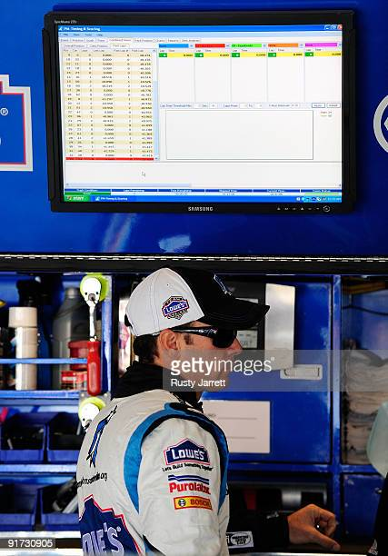 Jimmie Johnson driver of the Lowe's Chevrolet waits in the garage during practice for the NASCAR Sprint Cup Series Pepsi 500 at Auto Club Speedway on...