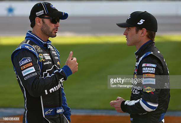 Jimmie Johnson driver of the Lowe's Dover White Chevrolet talks to Kasey Kahne driver of the Time Warner Cable Chevrolet on the grid during...