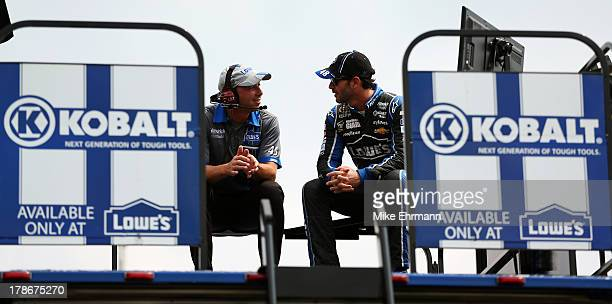 Jimmie Johnson driver of the Lowe's Dover White Chevrolet talks with his crew chief Chad Knaus on top of his team hauler during practice for the...