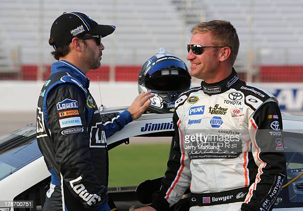 Jimmie Johnson driver of the Lowe's Dover White Chevrolet talks with Clint Bowyer driver the#15 RKMotorsCharlottecom Toyota during qualifying for the...